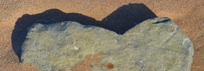 Stein in Herzform liegend im Sand